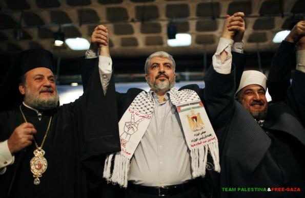 Hamas chief Khaled Meshaal raises hands with Greek Orthodox Archbishop Alexios (L) and senior Muslim cleric Hassan Al-Jojo (R) during a ceremony in Gaza City December 9 2012