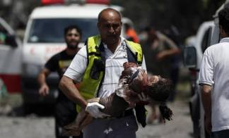 A baby girl being carry by a paramedics in Shujaiya Gaza July 20 2014