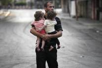 A Palestinian probably the father carrying his two babies Gaza July 2014