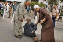 an elderly man being help by two other elderly males