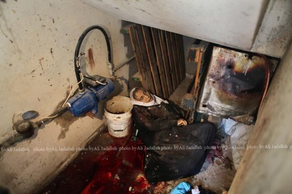 The body of a elderly woman, who medics said was killed during heavy Israeli shelling, is seen at her house in the Shejaia neighborhood, which was heavily shelled by Israel during fighting, in Gaza City July 20, 2014. At least 50 Palestinians were killed on Sunday by Israeli shelling in a Gaza neighborhood, where bodies were strewn in the street and thousands fled for shelter to a hospital packed with wounded, witnesses and health officials said. Militants kept up their rocket fire on Israel, with no sign of a diplomatic breakthrough toward a ceasefire in sight. REUTERS/Ali Hassan