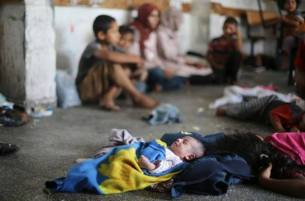 Palestinian and a baby seen sleeping on the floor at the UNRAWA building being used as shelter Gaza July 20 2014