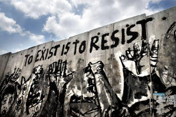 "The apartheid wall art ""To exist is to resist"" reads in bold red letters"