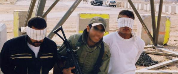 An Israeli soldier poses with Palestinian detainees in an undated photo taken by an Israeli soldier and made available by the campaign group Breaking the Silence.
